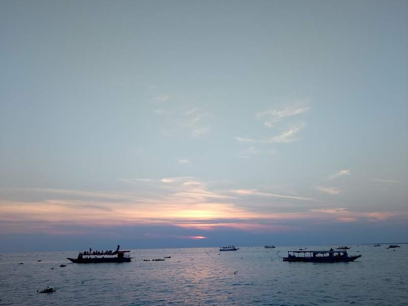 大小さまざまなボートで夕日鑑賞をする人々